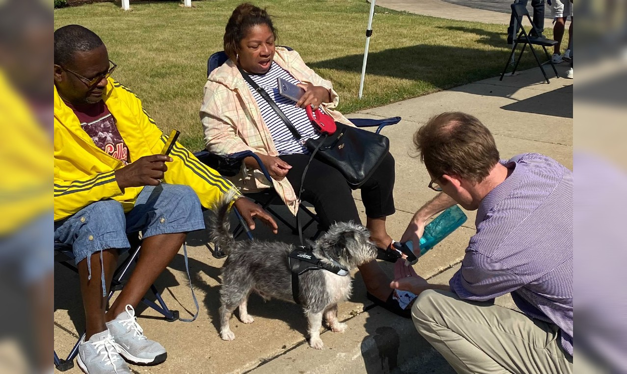 Senate Candidate Dem. Tom Nelson gives water to a thirsty pooch Saturday during the Juneteenth Day parade in Milwaukee.